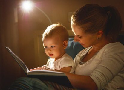 Mom reading to her baby in bed with a night light.