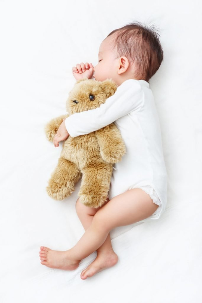 Sleeping Baby sucking its thumb holding a Teddy Bear